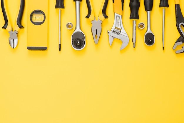 Gele en zwarte handige tools (pilers en schroevendraaier) geïsoleerd op gele achtergrond