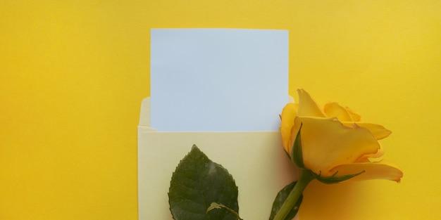 Gele envelop met een wit mockup-vel en gele roos ernaast op de verhelderende achtergrond van de kleur van het jaar 2021. sjabloon voor nieuwsbrieven en andere e-mailontwerpen.