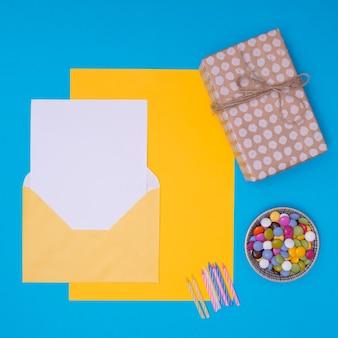 Gele envelop met verjaardagsuitnodiging op blauwe achtergrond