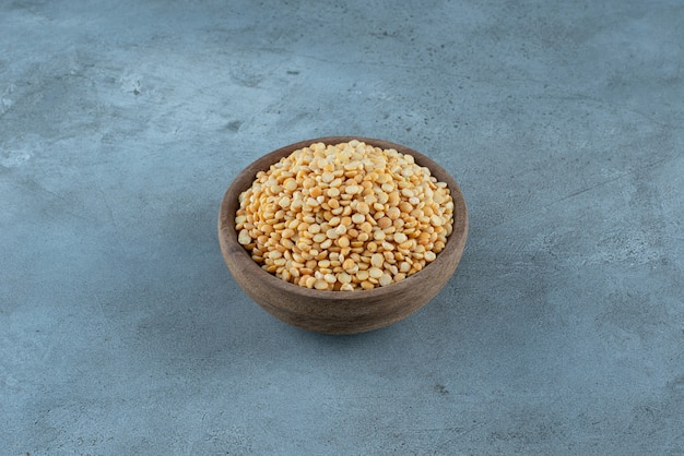 Gele erwtenbonen in een houten kop op blauwe achtergrond. hoge kwaliteit foto