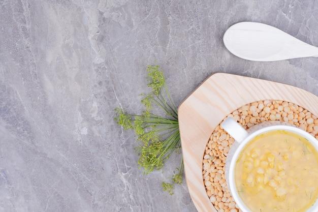 Gele erwtenbonen soep in een witte kop op het marmer