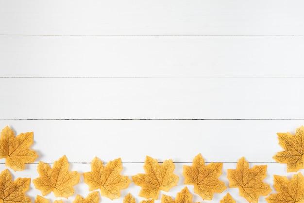 Gele esdoornbladeren op witte woode