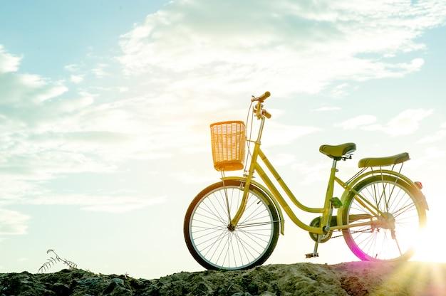 Gele fiets en zonsondergang in de avond van de winter met zeer belangrijke exemplaarruimte