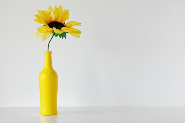 Gele fles met zonnebloem op witte achtergrond