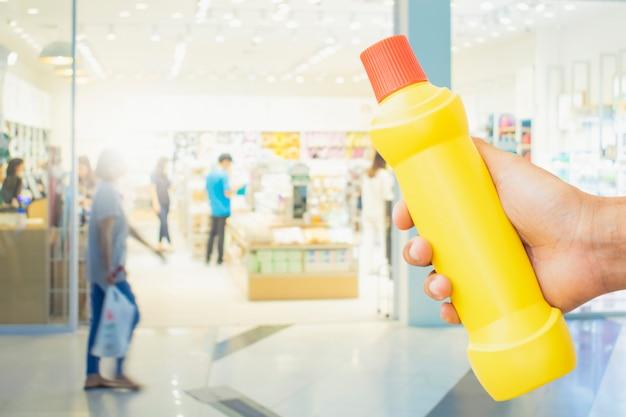 Gele fles voor het schoonmaken van personeel in huis onscherpe achtergrond metafoor voor het reinigen weg met ziektekiemen in de badkamer