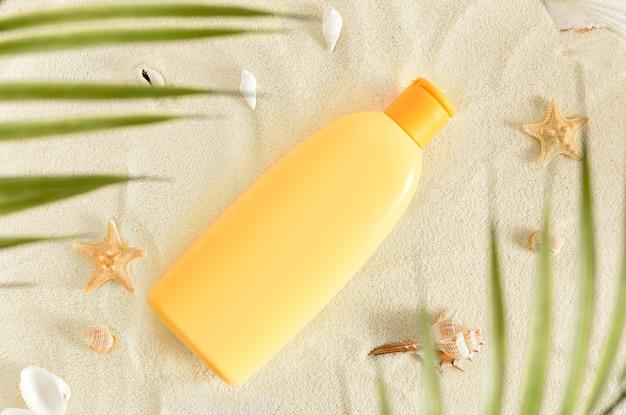 Gele fles zonnebrandolie op wit zand met schelpen