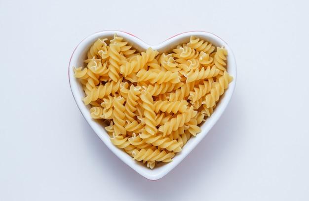Gele fusilli pasta in een hartvormige kom op een witte tafel. plat lag.