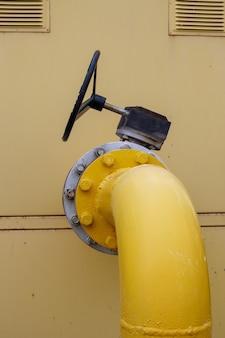 Gele gasleiding met een kraan. hulpstukken voor oliepijpleidingen in de olie- en gasindustrie. olie- en gasverwerkingsfabriek met pijpleidingfittingen. industriële veiligheidsklep.