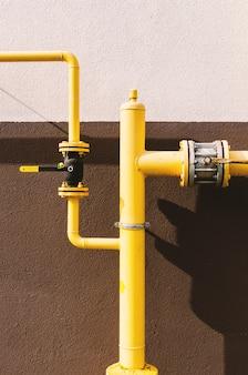 Gele gasleiding met kraan gaat langs de gevel van een nieuw gebouw met meerdere verdiepingen.