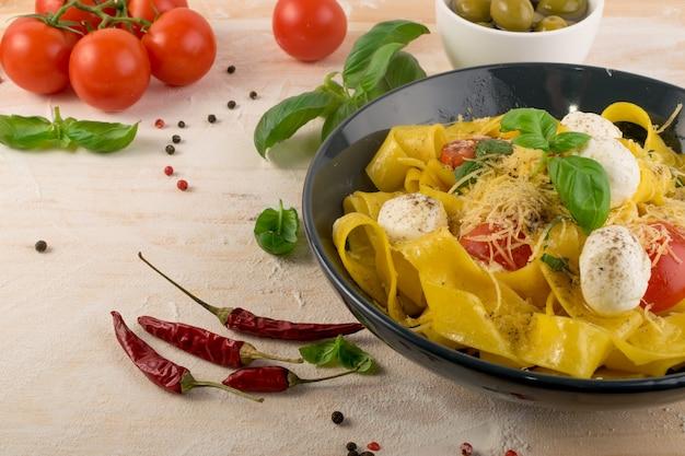 Gele gekookte pasta pappardelle, fettuccine of tagliatelle in zwarte kom. ei zelfgemaakte lintnoedels of macaroni met tomaten, basilicum en mozzarellaballetjes