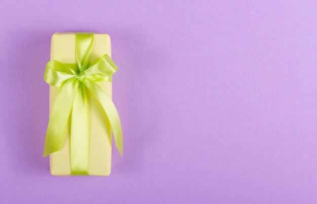Gele geschenkdoos met een groene strik op een paarse achtergrond.