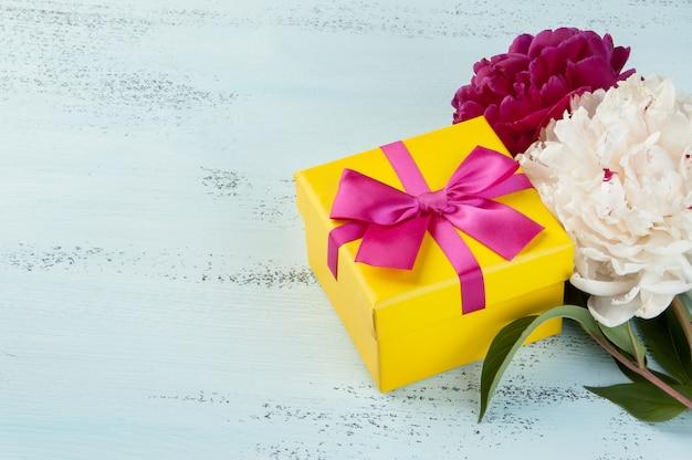 Gele geschenkdoos met strik en pioenrozen