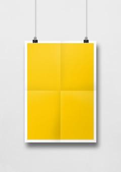 Gele gevouwen poster die met clips aan een witte muur hangt.