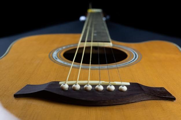 Gele gitaarplectrum verscholen in gouden akoestische gitaarsnaren op een donkere houten toets.