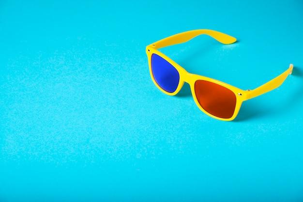 Gele glazen die op blauw worden geïsoleerd. 3d bril