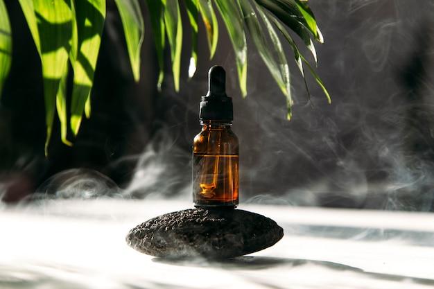 Gele glazen fles met cosmetische etherische olie en groene bladeren op de achtergrond