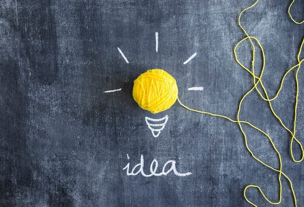 Gele gloeilamp gemaakt met bal van garen met idee tekst op schoolbord