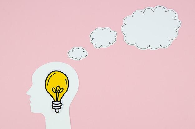 Gele gloeilamp in een hoofd met een tekstballon