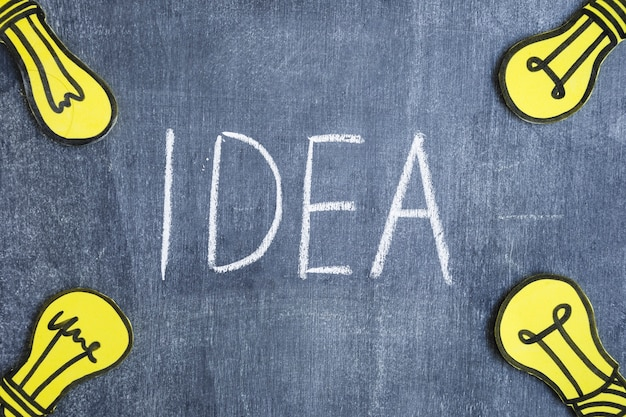 Gele gloeilampen op de hoek van bord met het idee van het tekstwoord dat met bord wordt geschreven
