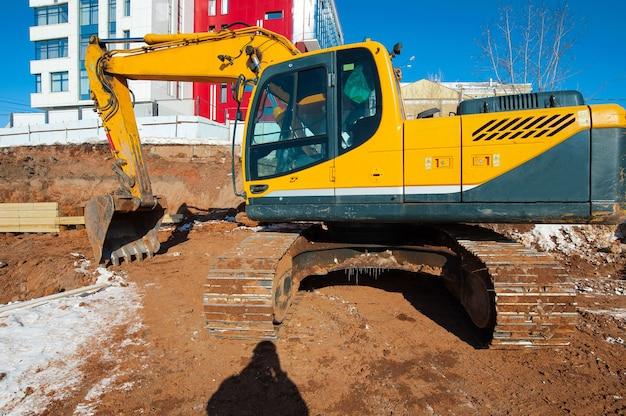 Gele graafmachine op een bouwplaats in de winter