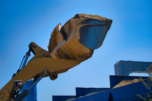 Gele graafmachine op een bouwplaats tegen blauwe hemel.