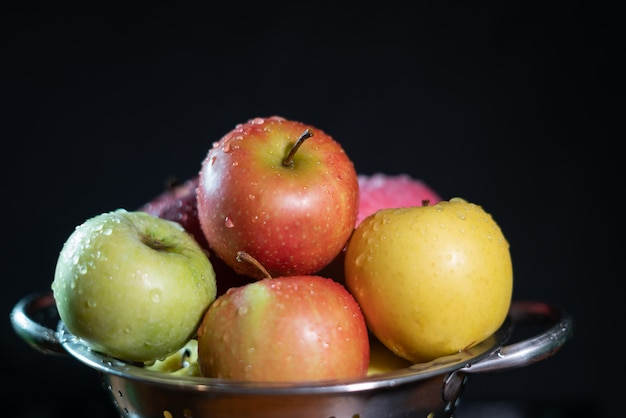 Gele, groene en rode appels tegen de zwarte achtergrond