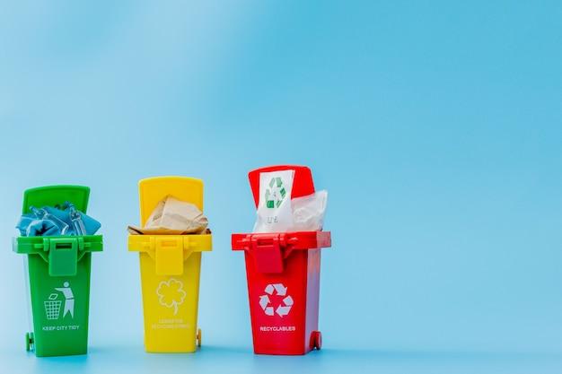 Gele, groene en rode prullenbakken met kringloopsymbool op blauwe achtergrond. houd de stad netjes, laat het recyclingsymbool achter. natuurbeschermingsconcept.