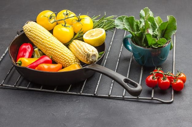 Gele groenten in koekenpan, greens in mok en een takje rode tomaten op metaalgrill.