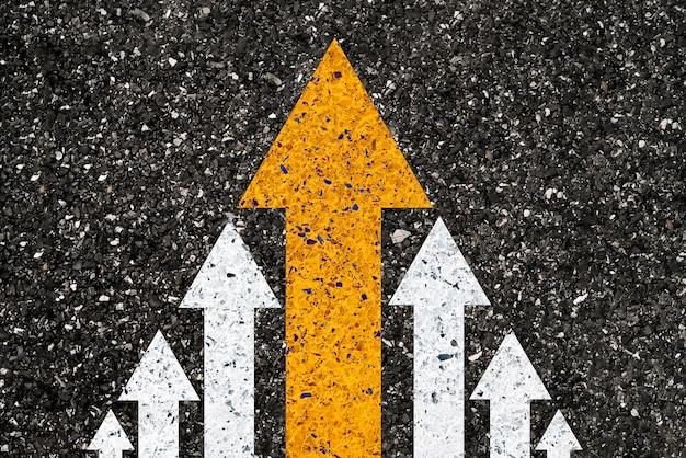 Gele grote pijlbeweging die leidt van kleine witte pijl op wegasfalt voor leiderschapsconcept.