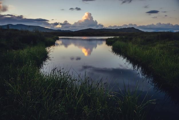Gele grote wolk in de vorm van een explosie boven het bergmeer in de buurt van groen gras op de voorgrond. geweldige gigantische wolk weerspiegeld in meerwater bij zonsopgang. enorme wolk van verhelderende kleur in de hemel met dageraadgradiënt.