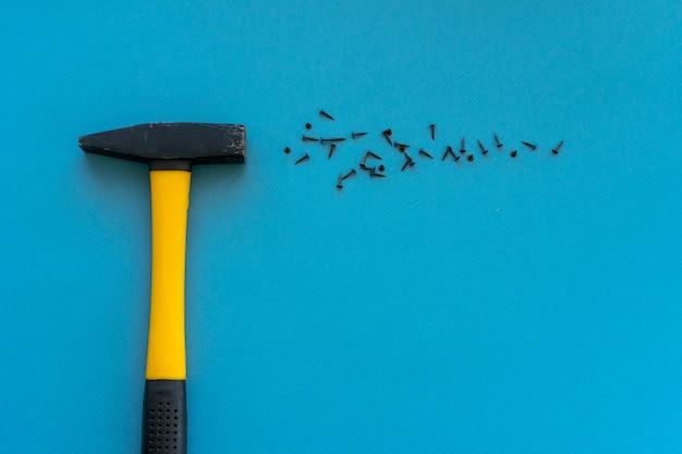 Gele hamer en spijkers zijn verspreid over het blauwe oppervlak