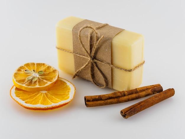 Gele handgemaakte zeep, droge stukjes sinaasappel en pijpjes kaneel op een witte achtergrond.