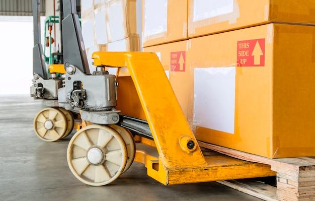 Gele handpallettruck met verzenddozen op pallet.