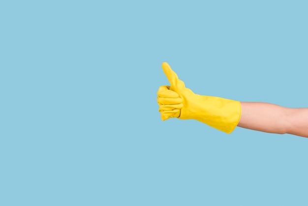 Gele handschoenenhand die duim op gebaar tonen tegen blauwe achtergrond