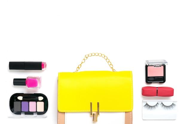 Gele handtas met accessoires voor vrouwen. zonnebril, lippenstift, blush, scrunchy, geïsoleerde borstels. bovenaanzicht plat leggen