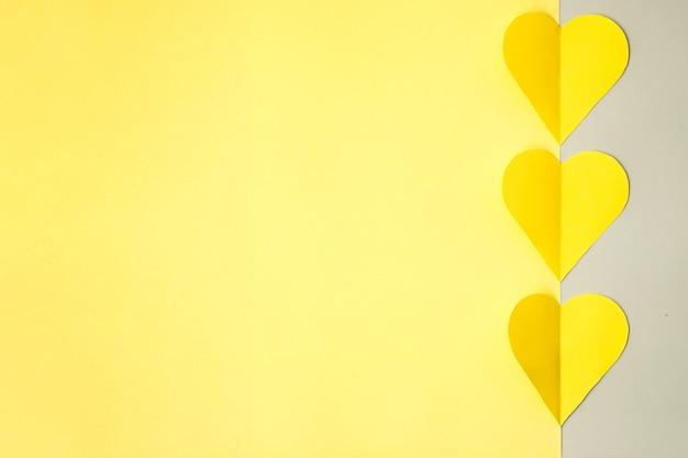 Gele harten gesneden uit gekleurd papier op een grijze achtergrond