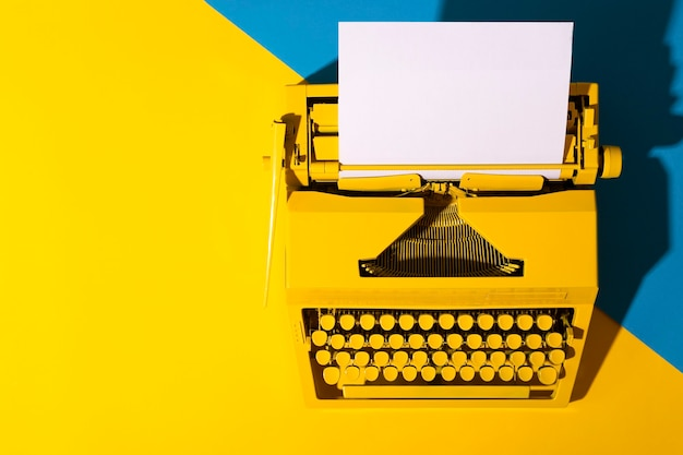 Gele heldere typemachine op een geel en blauw oppervlak