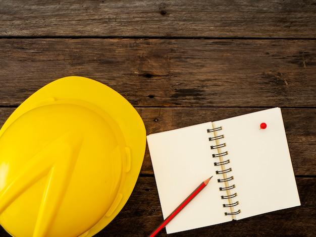 Gele helm en potlood op notebook bovenaanzicht