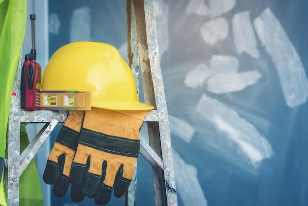 Gele helm met waterniveau, handschoenen en radio die op de vouwladder zijn geplaatst.
