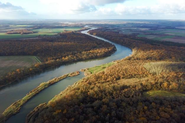 Gele herfst bos en blauwe rivier, bovenaanzicht, herfst landschap