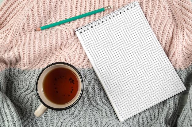Gele herfstbladeren, een kopje thee en een notitieblok op een getextureerde trui