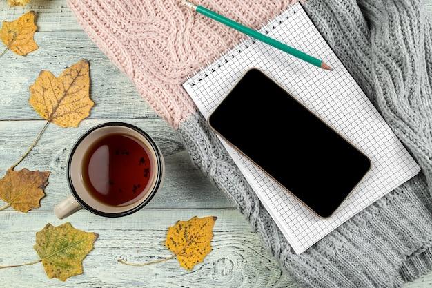 Gele herfstbladeren, een kopje thee en een smartphone op een oude houten achtergrond