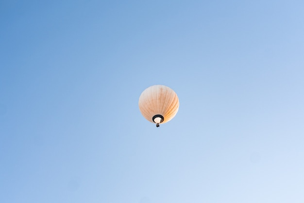 Gele hete luchtballon die in duidelijke blauwe hemel vliegt