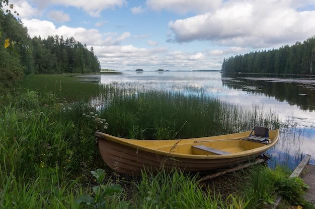 Gele houten boot aan de oever van een pittoresk meer en een weerspiegeling van wolken