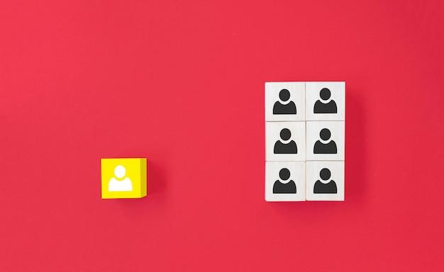 Gele houten kubus met persoonspictogram onderscheiden zich van de menigte op blauwe achtergrond