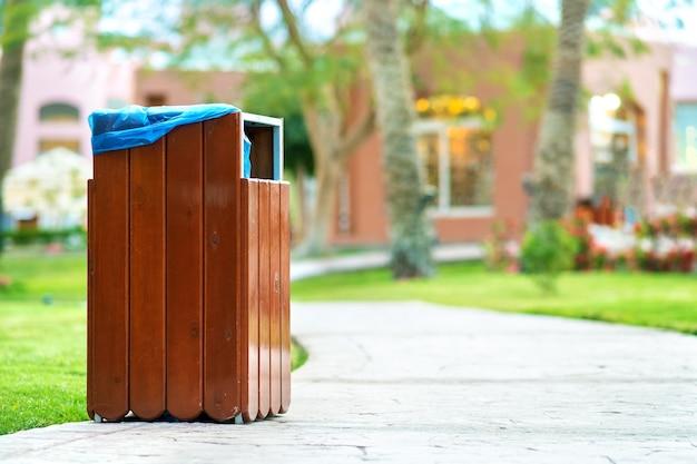 Gele houten vuilnisbak buiten aan de kant van de stoep in het park.