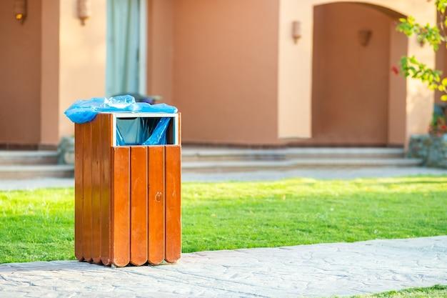 Gele houten vuilnisbak buiten aan de kant van de stoep in het park