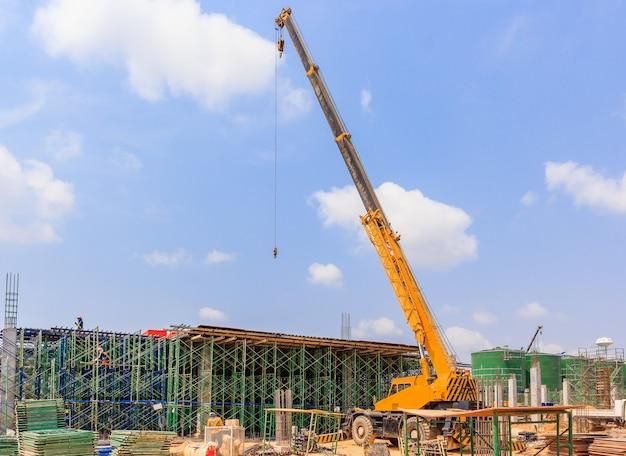 Gele hydraulische vrachtwagenkraan die zich op een bouwwerf in aanbouw bevinden.