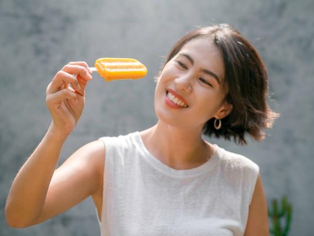 Gele ijslolly in de hand van een mooie, gelukkige aziatische vrouw met een casual wit mouwloos shirt, buitenshuis. aantrekkelijke vrouw die ijslollys toont. glimlachend vrouwtje genieten van ijslolly in de zomer.