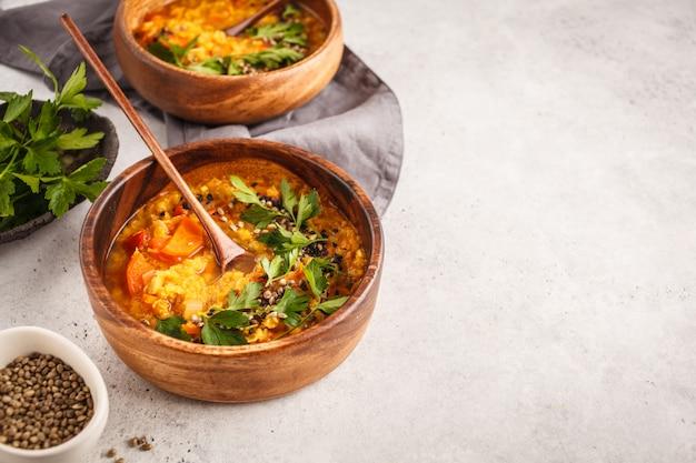 Gele indiase vegan linzensoep kerrie met peterselie en sesam in een houten kom, kopie ruimte.